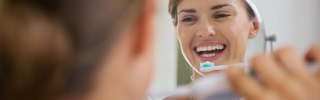 Frau putzt Zähne Spiegel