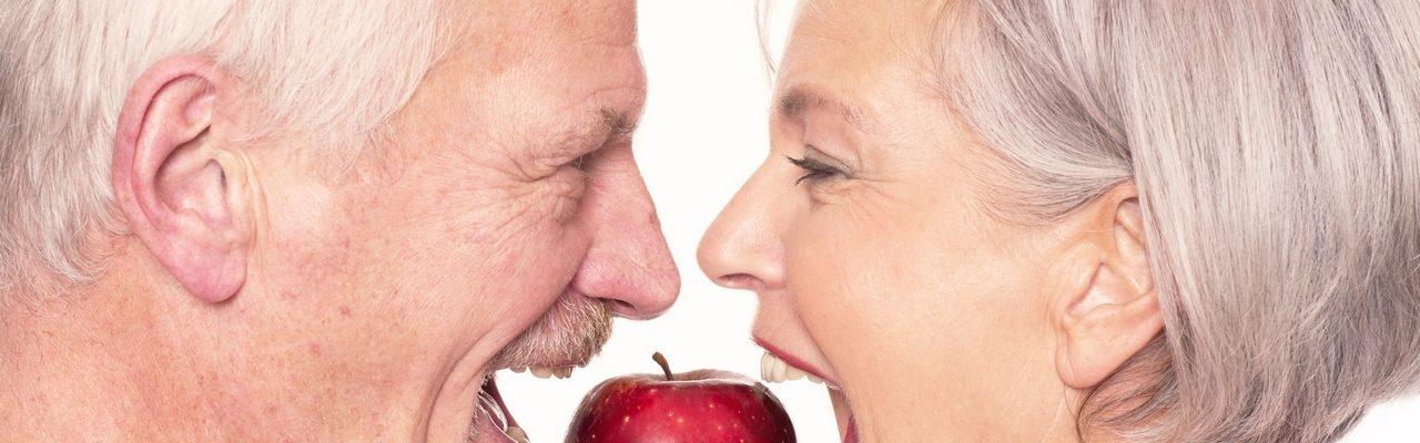 Älteres Pärchen beißt in Apfel