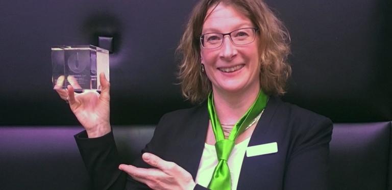 Katrin Schütterle hält Auszeichnung für goDentis hoch