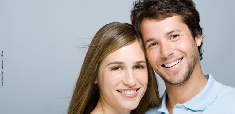 glückliches Paar nach Prophylaxe-Behandlung mit strahlend weißen Zähnen